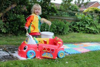 toddler washing toy car in garden