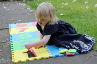 toddler with foam hopscotch squares